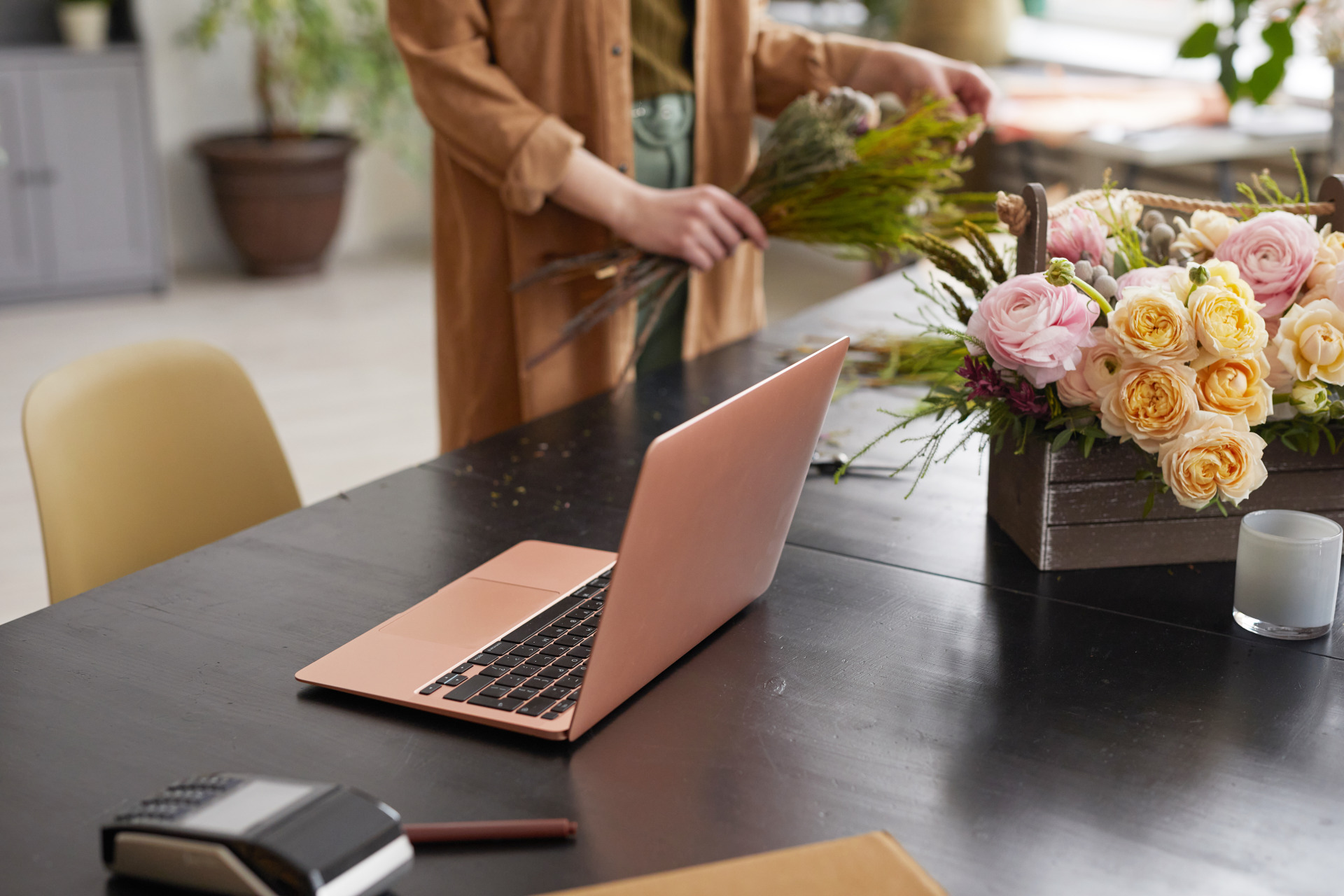 Woman running a florist business with a laptop out - Small Business SEO - Eyler Creative